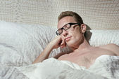 Tired naked handsome mid-ages man slept even not to pull off the eyeglasses. — Stock Photo