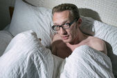 Frightened naked young man under the blanket — Stock Photo