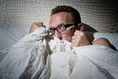 Frightened naked man under the blanket — Stock Photo
