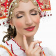 Coquettish young woman portrait  in russian traditional costume --  red sarafan and kokoshnik — Stock Photo #51536483
