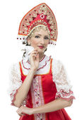 Smile coquettish young woman portrait  in russian traditional costume --  red sarafan and kokoshnik. — Stock Photo