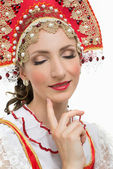 Coquettish young woman portrait  in russian traditional costume --  red sarafan and kokoshnik — Stock fotografie