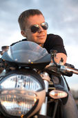 Romantic portrait handsome biker man in sunglasses sits on a bike on a sunset near lake — Stockfoto