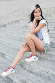 Young teenage girl with headphones,black long hair and jeans sitting on steps alone with rueful smile. — Stock Photo