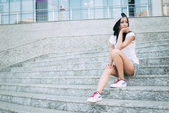 Young teenage girl with headphones,black long hair and jeans sitting on steps alone with rueful smile. — Stock fotografie