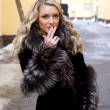 Beautiful blond model girl in fur coat on the city background smoking — Stock Photo #28891843