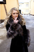 Beautiful blond model girl in fur coat on the city background smoking — Stock Photo