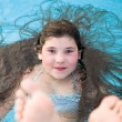 Preteen little girl with long dark hair in the swimming pool — Stock Photo #43681223