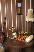 Retro room interior with wooden chess pendulum wall clock and dial phone — Stock Photo