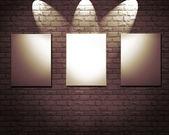 Blank frames on stone wall illuminated spotlights — Stockfoto