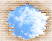 Hole in a brick wall against the sky — 图库照片