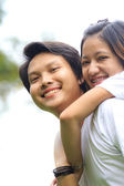 Young woman embracing man from behind in park — Stock Photo