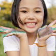 Asian little girl with hands painted in colorful paints — Stock Photo #27681161