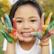 Asian little girl with hands painted in colorful paints — Stock Photo #27683429