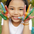 Asian little girl with hands painted in colorful paints — Stock Photo #27683511