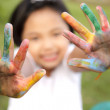 Asian little girl with hands painted in colorful paints — Stock Photo