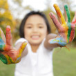 Asian little girl with hands painted in colorful paints — Stock Photo #27684515