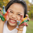 Asian little girl with hands painted in colorful paints — Stock Photo #27684535