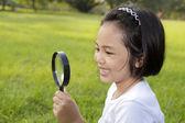 Asiática niña sosteniendo una lupa en el exterior — Foto de Stock