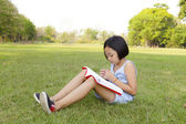 Asian little girl reading book in the park — Stock Photo
