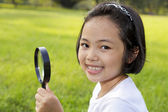 Asian little girl holding a magnifying glass in outdoor — Stock Photo