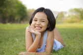Asian little girl relax and smiling happily in the park — Stock Photo