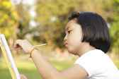 Asian little girl painting in in the park — Stock Photo
