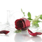 Red rose and broken glass of wine on white background — Stock Photo
