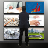 Businessman standing looking at the TV screen — Stock Photo
