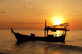 Silhouette of fishing boat at sunset — Stock Photo