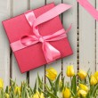 Red gift box with yellow tulips — Stock Photo