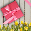 Red gift box with yellow tulips — Stock Photo #30246763