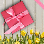 Red gift box with yellow tulips — Stok fotoğraf