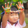 Little girl with hands painted in colorful paint  — Stock Photo