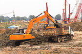 Excavator and truck — Stock Photo