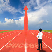 Businessman standing with success on running track — Stock Photo
