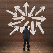 Businessman looking at arrows — Stok fotoğraf