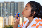 Little girl is blowing bubbles — Stock Photo