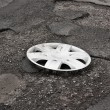 Wheel cover clipped on the damaged road — Stock Photo #35887397