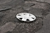 Wheel cover clipped on the damaged road — Stock Photo