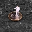Miniature figure businessman  on euro — Stock Photo