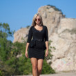 Beautiful young blond woman wearing black dress — Stock Photo