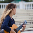 Teenage girl playing acoustic guitar outdoors — Stock Photo