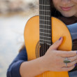 Teenage girl with a yellow wooden acoustic guitar outdoors — Stock Photo #34090643