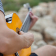 Man playing acoustic guitar close up outdoors — Stock Photo #34090679