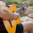 Man playing acoustic guitar close up outdoors — Stock Photo