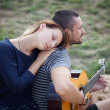 Man playing acoustic guitar for girl outdoors — Stock Photo