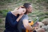 Jouer de la guitare acoustique pour l'extérieur de la fille de l'homme — Photo