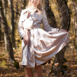 Stock Photo: Beautiful blond young womwearing cloak outdoors