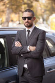 Handsome young businessman in suit standing near car — Stock Photo